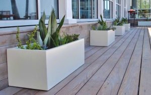 Line of white rectangular planters on a wooden outdoor patio