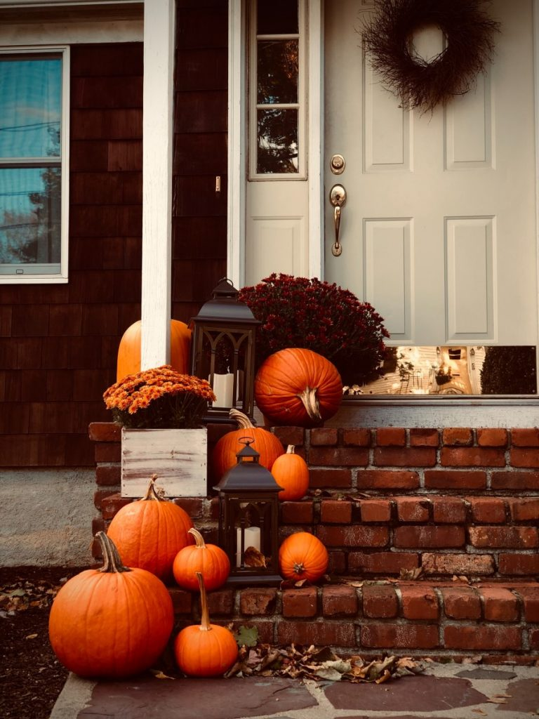 front porch decorated with lanterns pumpkins and colorful mums for the fall season
